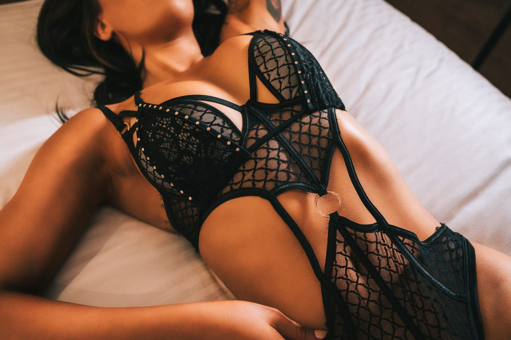Woman in lacy black lingerie busty lying on bed